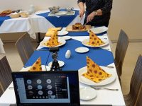 úkazka praktické výuky odborného výcviku distanční formou, kdy učitelka předvádí porcování a servírování pokrmu